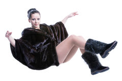 Woman in luxury black color fur coat and shoes flying in the air Royalty Free Stock Photos
