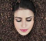 Beautiful face among coffe beans Stock Photography