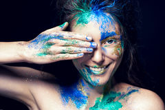 Beautiful face with colored paint on a black background. Beautiful girl. Colorful makeup. Fashionable woman. Toned image royalty free stock photography