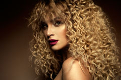 Beautiful face of a fashion model with blue eyes.Curly hair. Red lips. stock photos