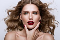 Beautiful face of a fashion model with blue eyes.Curly hair. Red lips. stock images
