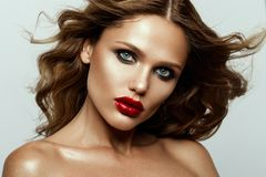 Beautiful face of a fashion model with blue eyes.Curly hair. Red lips. royalty free stock photos