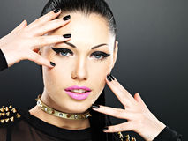 Beautiful face of fashion woman with black nails and bright make. Up.  Sexy stylish girl with bracelet thorns on the neck Royalty Free Stock Photos