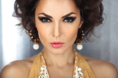 Beautiful face of a glamour woman with smoky eyes make-up. Beauty portrait young girl. Beautiful woman with evening make-up and curly hair and yellow dress with stock image