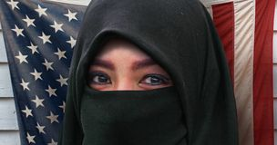 Beautiful face of Muslim woman in traditional Islam burqa or burka head scarf posing cheerful and happy smiling isolated on United. States American flag royalty free stock image