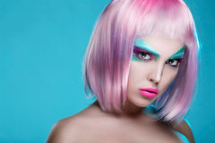 Beautiful face of puppet girl with face art in pink wig on seren Stock Image