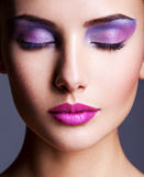 Beautiful face with purple eye make-up. fashion makeup stock photography