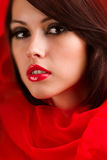Beautiful face sweet lips folds of red cloth. Wrapped in scarlet cloth face of a beautiful young girl with a glamorous make-up, where the bright red lips royalty free stock images