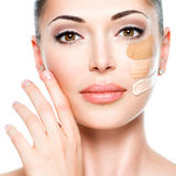Beautiful face of  woman with cosmetic foundation on a skin. Stock Photos