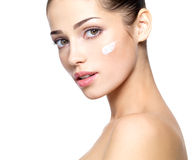 Beautiful face of woman with cream on cheek. Beautiful face of young woman with cosmetic cream on a cheek. . Skin care concept. Closeup portrait isolated on Stock Photos