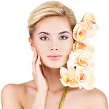 Beautiful face of  woman with healthy skin and pink flowers Royalty Free Stock Images