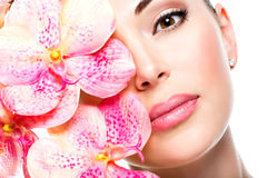 Beautiful face of  woman with healthy skin and pink flowers Stock Images