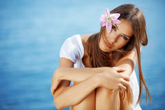Beautiful face of woman with lily in her hair Royalty Free Stock Photography