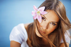 Beautiful face of woman with lily in her hair Royalty Free Stock Images
