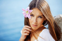 Beautiful face of woman with lily in her hair Stock Photography