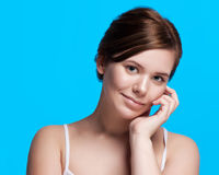 Beautiful face of young adult woman with clean fresh skin -  on blue Stock Photo