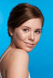 Beautiful face of young adult woman with clean fresh skin -  on blue Stock Image
