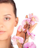 Beautiful face of young brunette woman with healthy skin and pink orchid Royalty Free Stock Image