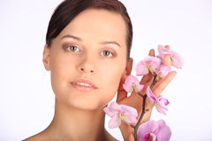 Beautiful face of young brunette woman with healthy skin and pink orchid Royalty Free Stock Photo