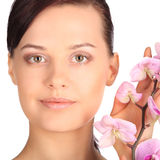 Beautiful face of young brunette woman with healthy skin and pink orchid Stock Images