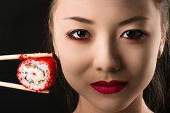 Beautiful face young Korean girl with roll, bright makeup. Isolated on black background Stock Photos