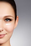 Beautiful face of young woman with cosmetic cream on a cheek. Sk Stock Photo