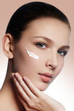 Beautiful face of young woman with cosmetic cream on a cheek. Sk Royalty Free Stock Photos