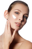 Beautiful face of young woman with cosmetic cream on a cheek. Royalty Free Stock Images