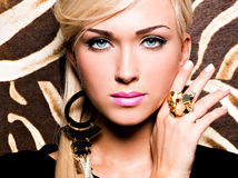 Beautiful face of young woman with fashion makeup. Closeup portrait of beautiful face of sexy woman with fashion makeup and gold ring on finger Stock Images