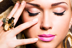 Beautiful face of young woman with fashion makeup. Closeup portrait of beautiful face of sexy woman with fashion makeup and gold ring on finger Royalty Free Stock Photography