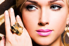 Beautiful face of young woman with fashion makeup. Closeup portrait of beautiful face of sexy woman with fashion makeup and gold ring on finger Royalty Free Stock Images