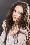Beautiful face of young woman with long curly hair. Stock Image
