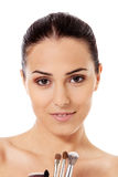 Beautiful face of young woman with make up brush. Royalty Free Stock Images