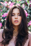 Beautiful face of young woman with makeup over the pink flowers. Portrait of the pretty healthy skin girl.Outdoor Royalty Free Stock Photography