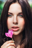 Beautiful face of young woman with makeup over the pink flowers. Portrait of the pretty healthy skin girl.Outdoor Royalty Free Stock Photo