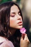Beautiful face of young woman with makeup over the pink flowers. Portrait of the pretty healthy skin girl.Outdoor Stock Image