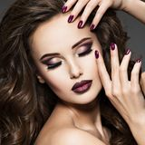 Beautiful face of woman with maroon makeup. Beautiful face of young woman with maroon makeup. Portrait of gorgeous girl with vinous nails royalty free stock photography