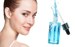 Beautiful face of young woman near blue cosmetic bottle. stock photos