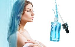 Beautiful face of young woman near blue cosmetic bottle. stock photography