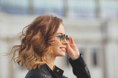 Beautiful face of young woman in round glasses and in black leather jacket. Outdoor portrait in the city Royalty Free Stock Photos
