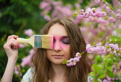 A beautiful fair-haired girl stands in the garden of a blooming pink Sakura with her eyes closed and paints a brush of pink eyes. Horizontal photography stock photos