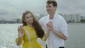 Cheerful young woman and man dance electrifying dance on a dock in a rainy weather stock footage