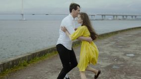 Happy girl and boy dance retro style on a pier with a lot of rain pools stock footage