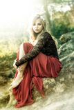 Beautiful fairy blonde dressed in a red sitting on the roccks. royalty free stock photo