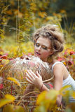 Beautiful fairy girl with golden cage in a forest Stock Image