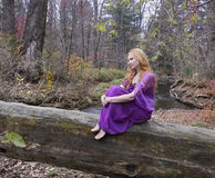 Beautiful fairy lady sitting on the tree by the river. Beautiful blonde girl sitting on the old log or tree in the autumn wood. Charming lady by the river royalty free stock image