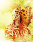 Fairy with wings on a flower. Beautiful fairy with wings on a flower in water. Sexy blonde butterfly woman Stock Photos