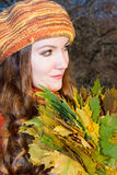 Beautiful fall woman. Portrait of girl with maple autumn leaves on nature Royalty Free Stock Image