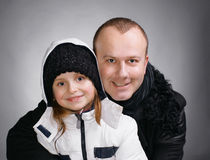 Beautiful family. Smiling father and daughter in winter outwear on a gray background royalty free stock photo
