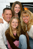 Beautiful Family. A beautiful family, father, mother and two daughters, smiling in front of their fireplace stock photos